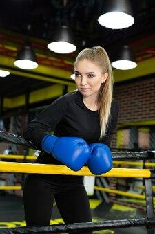 ボクシングのリングの中に立っている筋肉の体を持つ女性のボクサー