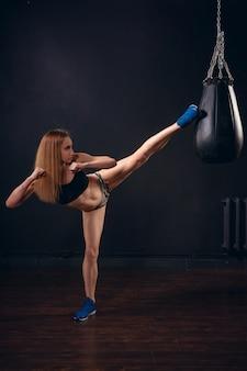Female boxer kicks the punching bag