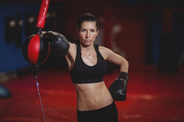 Female boxer leaning on speed boxing ball