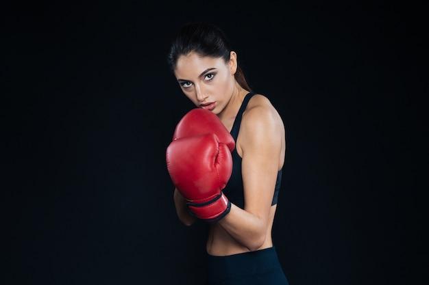 黒の背景でポーズをとる女性ボクサー