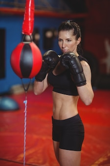 Female boxer practicing boxing with speed boxing ball