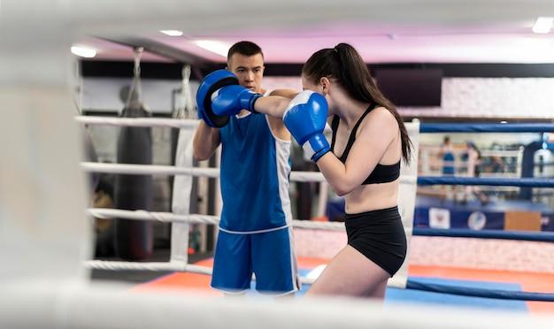 Pugile femminile che si esercita con l'istruttore accanto all'anello