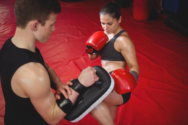 Pugile femminile che si esercita con l'istruttore