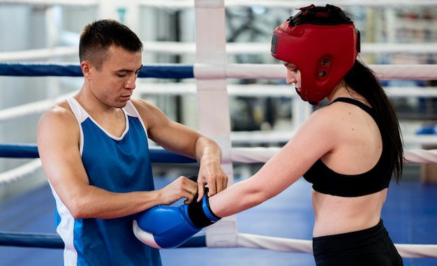 Female boxer putting on protecting gloves