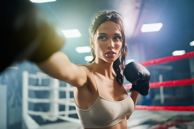 Female boxer showing hit in boxing gloves.