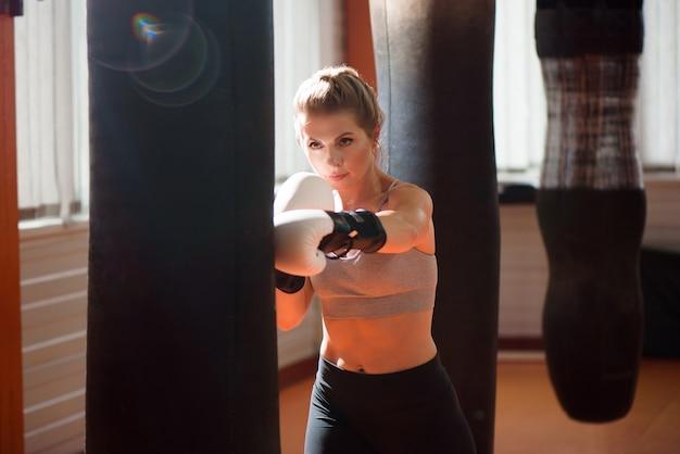 A female boxer train hard in a boxing studio.