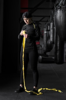 Female boxer trainer with elastic cord in the gym