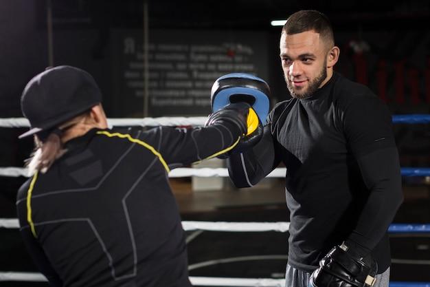 保護手袋を着用しながらリングで女性ボクサートレーニング