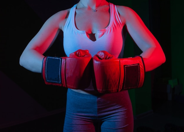 暗い壁にネオンブルーレッドライトで彼女の手にボクシンググローブを持つ女性ボクサー