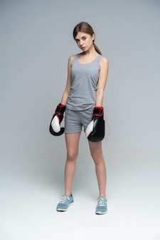 Female boxer with boxing gloves standing on grey looking down