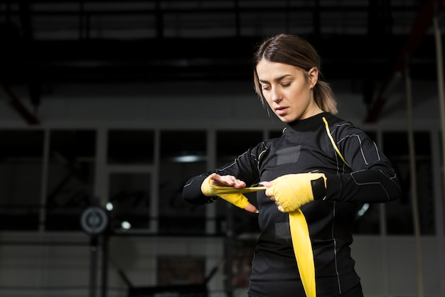 Female boxer wrapping her hand in preparation for practice