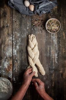 木製のテーブルトップビューに手で女性の編みこみの生地