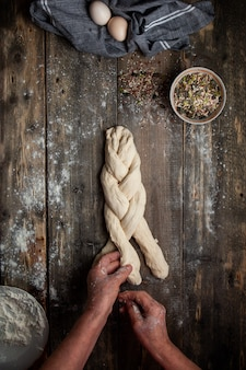 Female braiding dough with hands on wooden table top view