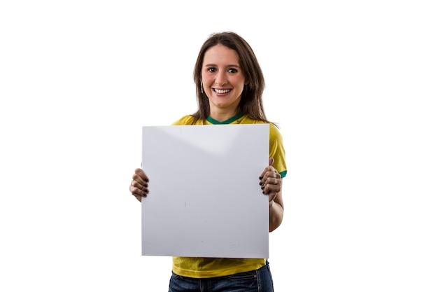 白いスペースに、空白のボードを保持している女性のブラジルのファン。
