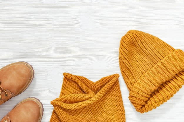 Female bright orange clothing, warm wool knitted scarf, cap and cozy shoes. shopping overview concept with copy space. fashion concept. top view. flat lay.