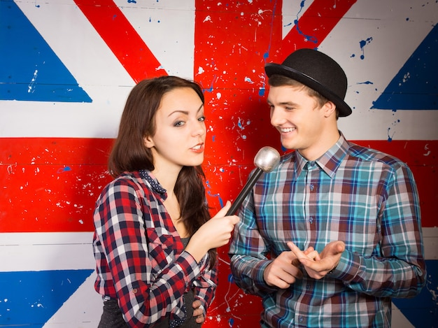 壁に描かれたユニオンジャックの旗の前で山高帽をかぶったハンサムな若い男にインタビューする女性の英国のチャットショーのホスト