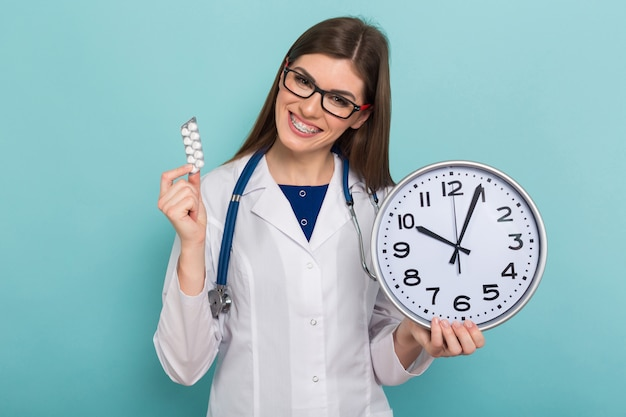 Female brunette doctor in glasses with clock