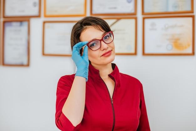 眼鏡と青い医療用手袋と卒業証書と白い壁に対してキャビネットでポーズをとる赤いコートの女性ブルネットの医者。