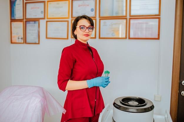 眼鏡と青い医療用手袋と赤いコートを着た女性のブルネットの医師が、血清のシステムに試験管を入れています。
