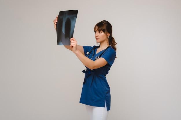 トモグラフィーx線フィルムを見ている女性のブルネットの医者。