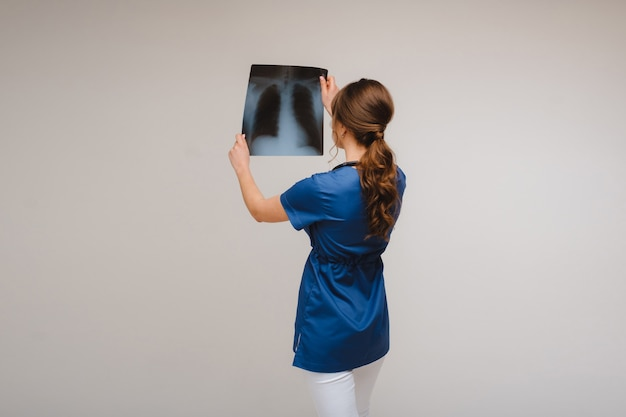 Female brunette doctor looking at tomography x-ray film.