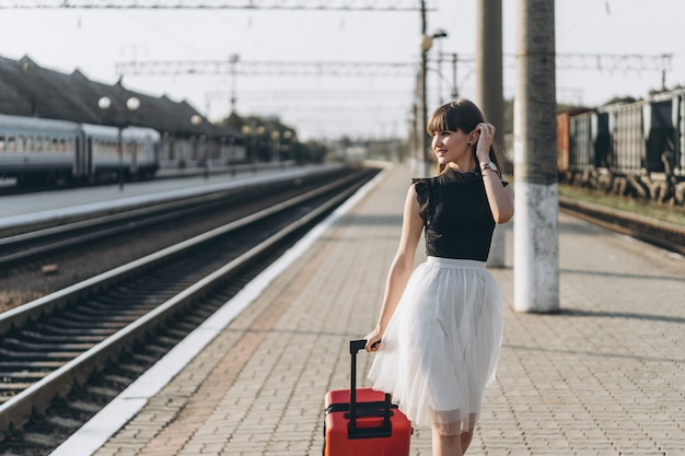 Female brunette traveler with red suitcase walking on raiway station