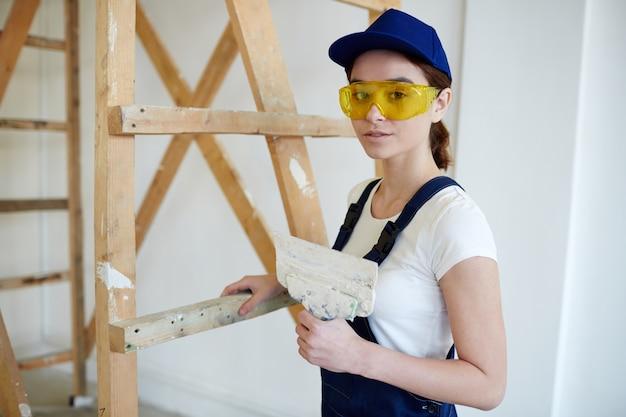 Женский строитель, выполняющий гипсовые работы