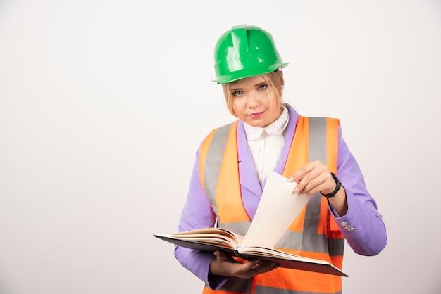 白い壁にタブレットを保持しているヘルメットの女性ビルダー。