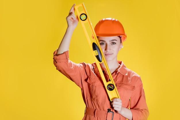 여성 건축업자 또는 안전모 및 안전 수리공은 건물 수준을 보유하고 있습니다.