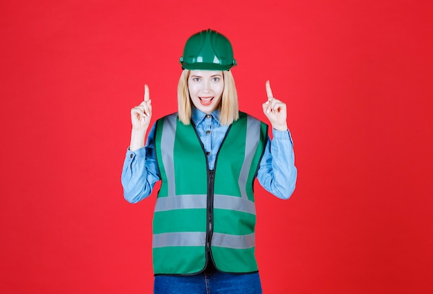Female builder in uniform, helmet and pointing up with fingers showing advertisement, surprised face and open mouth