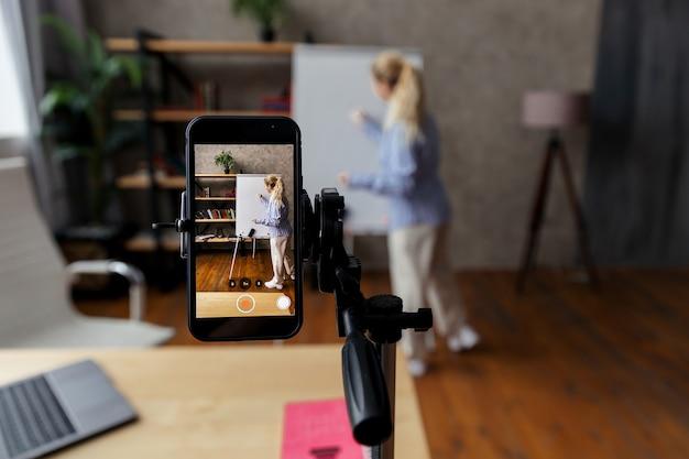 여성 비즈니스 코치, 튜터 실시 웨비나, 온라인 교육. 온라인 멘토가 비디오 강의를 진행합니다. 전화에 집중하십시오. 고품질 사진