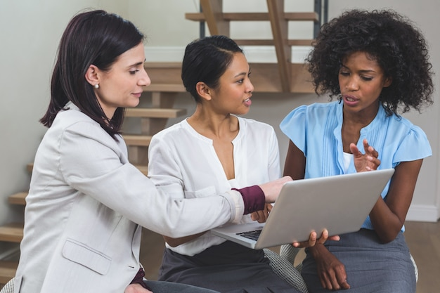 Female business colleagues discussing on laptop