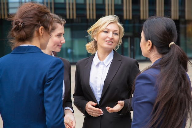Female business colleagues discussing project outdoors. businesswomen wearing suits standing together in city and talking. communication concept