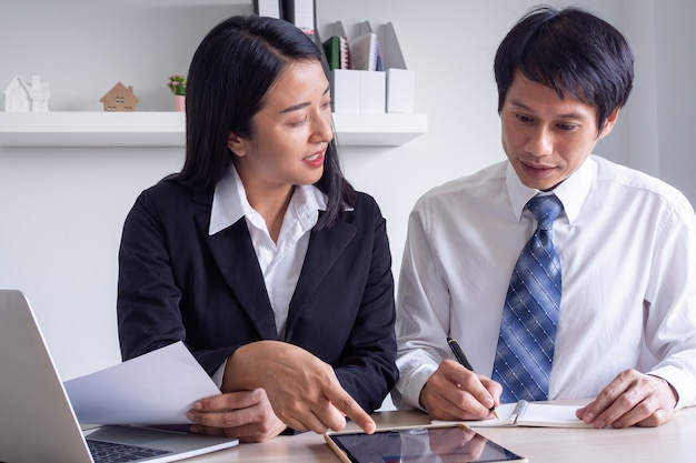 Female business consultant explains stock information chart for stock trading training for male business owners that uses stock trading or sme business growth.