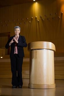 会議センターでスピーチをしながら身振りで示す女性経営者