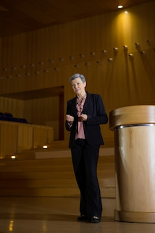 Female business executive gesturing while giving a speech at conference centre