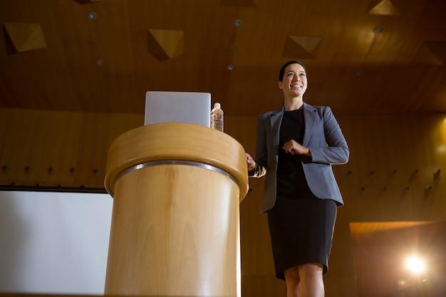 会議センターでスピーチをする女性経営者