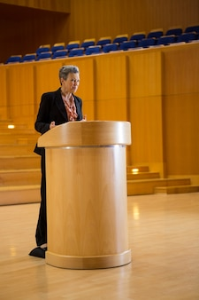 Female business executive giving a speech at conference center