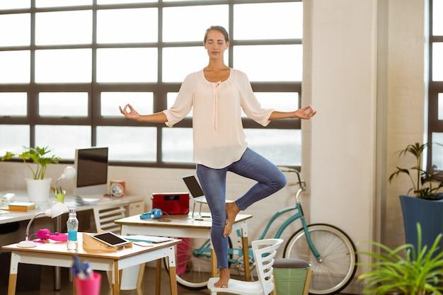 Female business executive performing yoga