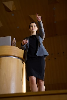 会議センターでスピーチをしながら指さしている女性経営者