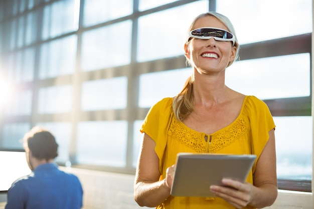 Female business executive in virtual reality video glasses using digital tablet