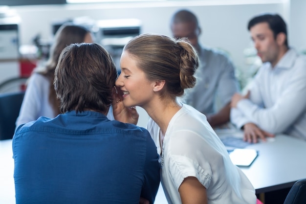 Женский руководитель бизнеса шепчет ее коллеге