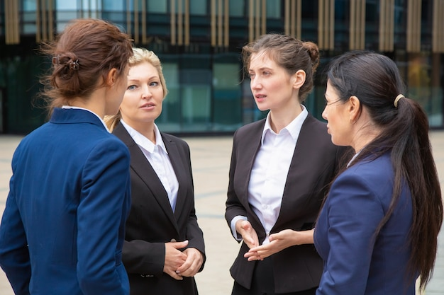 Female business group brainstorming outdoors. businesswomen wearing suits standing together in city and talking.