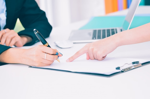 Female business hand signing on contract document