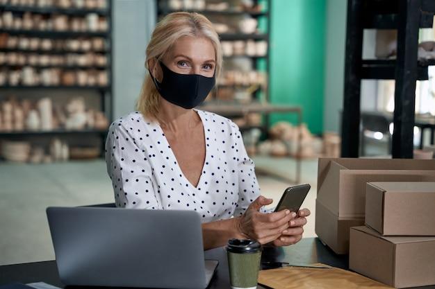 Владелец женского бизнеса в защитной маске держит мобильный телефон и смотрит в камеру во время