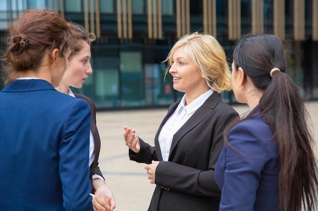 야외에서 거래를 논의하는 여성 비즈니스 파트너. 경제인 도시에서 함께 서서 이야기 정장을 입고. 기업 커뮤니케이션 개념