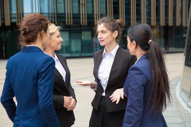 屋外でプロジェクトを議論する女性のビジネスチーム。街で一緒に立って話しているスーツを着ているビジネスウーマン。コミュニケーションとチームワークの概念