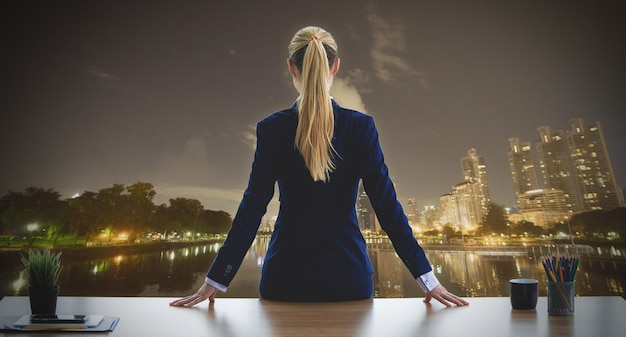 Female business woman is looking out the windows for success