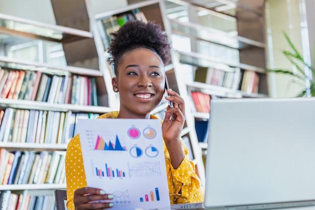 カジュアルウェアの女性ビジネスマンは、会計および事業計画の分析について机で働いています