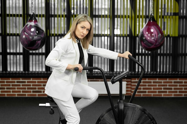 Female businesswoman in a white suit is engaged on an exercise bike in a boxing club.